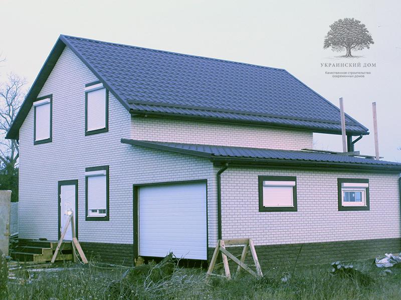 """Канадский дом из сип панелей - объект компании """"Украинский дом"""" в с. Курортное - дом с оконченной фасадной отделкой вид со стороны гаража"""